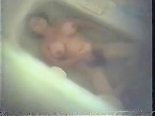 hirsute woman dildoing inside shower tube.